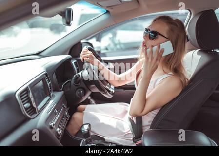 Femme fait appel, au cours de l'été lieu de stationnement situé près de centre commercial, infirmant en stationnement. Robe rose lunettes de l'écoute de message sur un