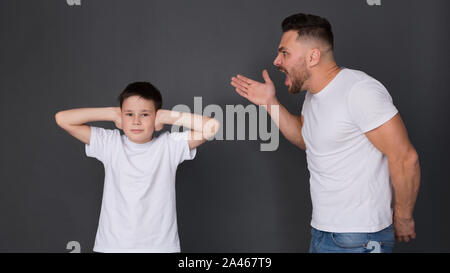 Père nerveux de crier sur son fils, garçon de fermer les oreilles Banque D'Images