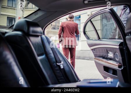 Jeune homme d'affaires est à l'extérieur et talking on mobile près de la limousine Banque D'Images