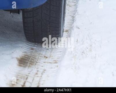Pneu de voiture sur une route d'hiver de neige closeup Banque D'Images