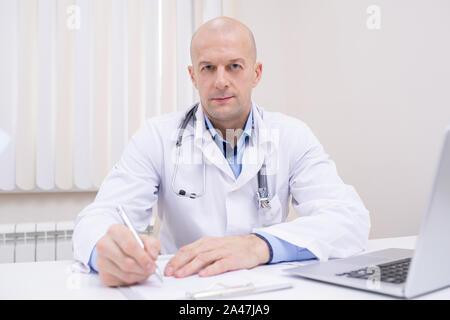 Bald middle aged certain médecin en séance de travail par blanchon Banque D'Images