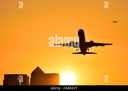 Avion au décollage de l'aéroport de London City avec un ciel d'or que le soleil se couche derrière les toits de Canary Wharf Banque D'Images