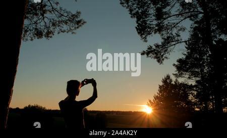 La prise de photo de silhouette de femme sunset with smartphone Banque D'Images