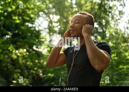 Close up of African sportsman à l'écoute de la musique avec un casque, en appréciant. Coureur d'exécution dans la forêt avec les yeux fermés. Homme avec corps sportif portant en noir t shirt.