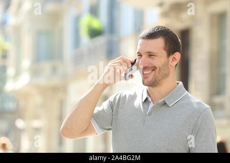 Happy man talking on mobile phone marche dans la rue Banque D'Images