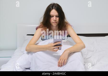 Adolescent fatigué girl sitting at home in bed looking at mobile phone. Banque D'Images