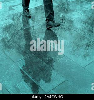 Réflexion floue les jambes et de l'ombre, silhouette d'un homme dans le trottoir humide, dans une flaque d'eau de pluie sur un pied Banque D'Images
