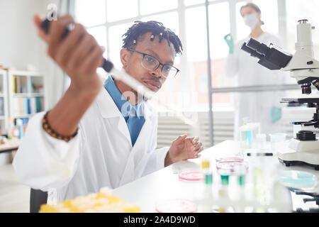 Portrait de jeune homme afro-américain travaillant dans la préparation d'échantillons d'essai de laboratoire pour la recherche médicale, copy space