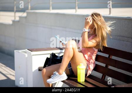 De la sportive à la recherche de téléphone intelligent, à l'extérieur. Femme Fitness se reposant après run dans la ville. Banque D'Images