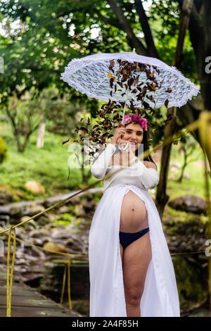 Belle femme enceinte latine 22-26 ans wearing white dress holding umbrella avec feuilles de tomber Banque D'Images