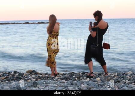 Limassol / Chypre - 15 août 2019: Deux jeunes filles posent pour des photos à l'aide de smart phone caméra sur windy beach at sunset Banque D'Images