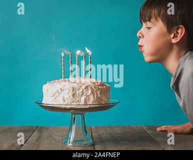 Boy blowing out candles on cake contre un fond bleu. Banque D'Images