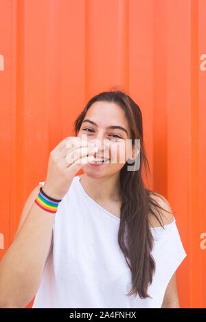 Souriante jeune femme appuyée contre un mur à l'extérieur Banque D'Images