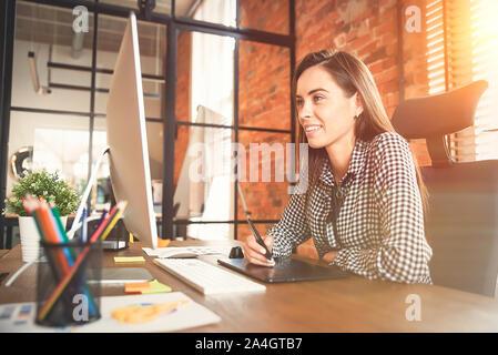 Jeune artiste designer graphique quelque chose de dessin sur tablette graphique au bureau