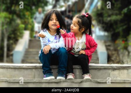 Deux jeunes filles s'asseoir et manger une sucette dans le parc, piscine d'été portrait. Meilleurs amis Banque D'Images
