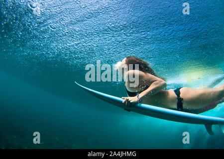 Coup de mouvement dynamique de femmes internautes en bikini noir avec plongée sous-marine surf vague en rouleau Banque D'Images