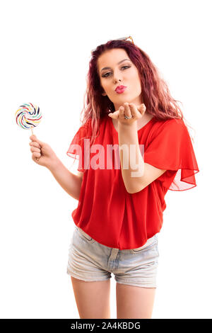 Belle jeune fille à la mode avec une lucette blowing a kiss à vous, isolé sur fond blanc. Banque D'Images