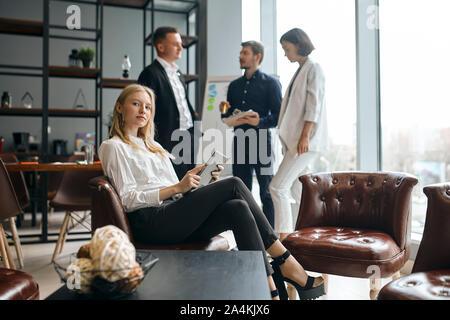 Confiant beautiul femme chef de l'équipe est assis sur le fauteuil avec bras croisés regardant la caméra. Trois personnes discutant le proj Banque D'Images