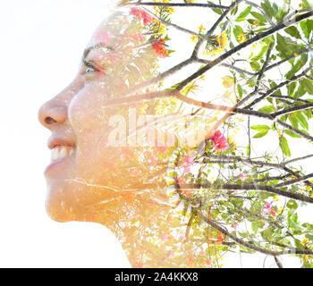 Profil de l'exposition double portrait d'un jeune, souriant la beauté naturelle combinée avec des branches d'arbres en bonne santé et de nombreuses petites fleurs, on a white background Banque D'Images