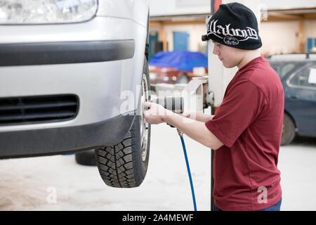Jeune homme changement des roues à technical college, la Norvège. Apprenti Banque D'Images