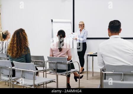 Smiling manager passe plus de graphiques et tableaux au cours d'une présentation au personnel dans une salle de réunion dans un bureau