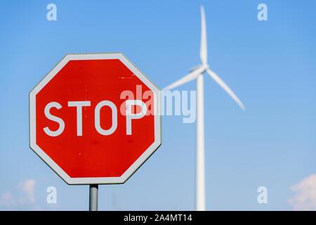 Panneau stop et éolienne sur arrière-plan Banque D'Images