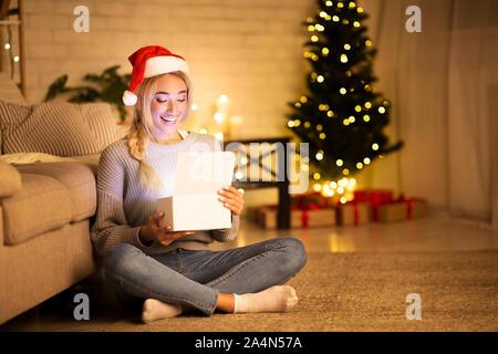 Le temps de Noël. Happy girl with santa hat boîte cadeau d'ouverture Banque D'Images