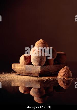 Truffes au chocolat dans de petits plats en bois saupoudré de cacao en poudre. Fond réfléchissant noir. Copier l'espace. Banque D'Images