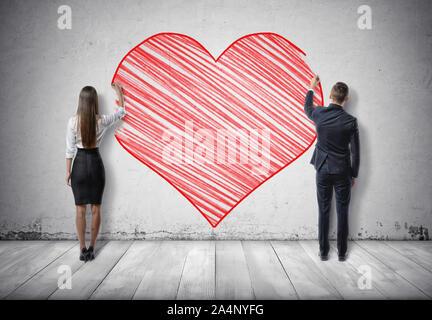 Businessman and businesswoman dimensions gros cœur rouge sur mur de béton Banque D'Images