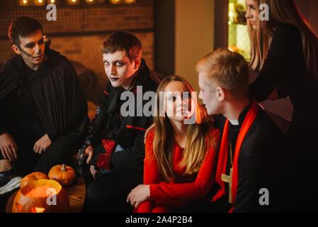 Guy en comte Dracula's Halloween costume est assis avec des amis dans un café Banque D'Images
