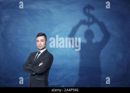Businessman standing et d'ombre sur le tableau noir derrière lui tenant le signe du dollar au-dessus de sa tête Banque D'Images