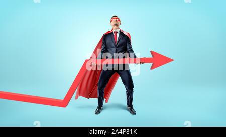 Un homme d'une cape qui coule rouge essayant de soulever une grande flèche rouge vers le haut sur fond bleu. Banque D'Images