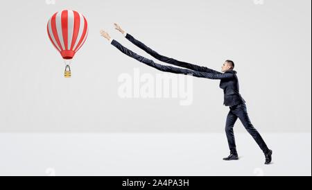 Un homme d'affaires en vue de côté, essayant d'attraper une grande montgolfière vol avec sa très longue durée d'armes. Banque D'Images