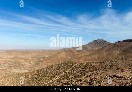 Donnant sur une chaîne de montagnes de l'Atlas au Maroc Gamme Moutnain. Certains petits arbustes et arbres vu en face d'un joli bleu ciel couvert par des nuages