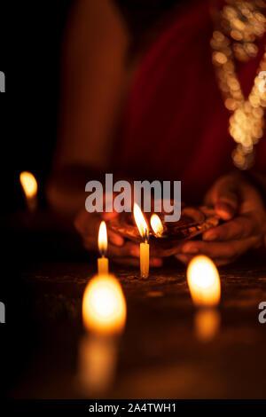 Le port de bijoux traditionnels indiens ménagère et éclairage des bougies avec diya ou d'argile sur lampe Diwali fête saison. Arrière-plan de dhanteras, dans Banque D'Images