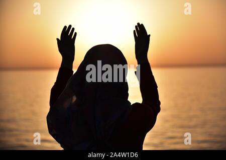 Silhouette d'une femme musulmane prier pendant le coucher du soleil sur le grand navire.vue arrière de la prière musulmane portant le hijab.