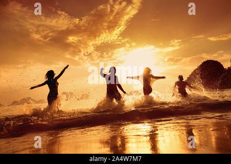Quatre amis heureux s'exécute et s'amusant à beau coucher de soleil mer plage