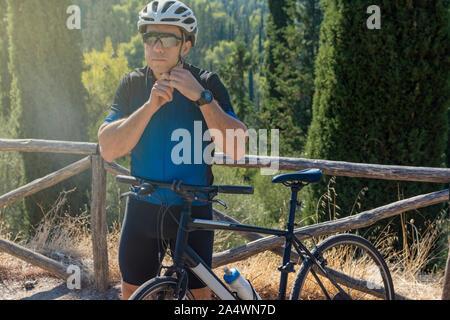 Cycliste homme mettre sur son casque avant de s'entraîner avec son vélo - préparation pour le sport