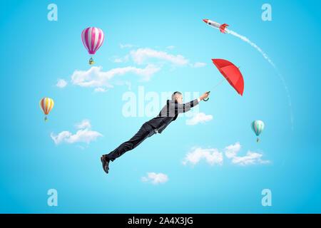 Young businessman holding parapluie rouge et voler haut dans le ciel bleu, avec des ballons à air chaud et de lance en arrière-plan. Banque D'Images