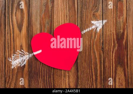 Carte de la Saint-Valentin pour la Saint-Valentin papier rouge coeur a été transpercé d'une flèche tracée à la craie sur les planches de bois Banque D'Images