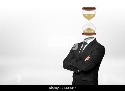 Un homme d'affaires avec ses bras repliés devant se dresse sur fond blanc et a la tête remplacée par un sablier. Banque D'Images