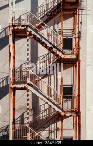 Old rusty metal avec la sortie d'urgence de l'immeuble vue depuis l'escalier de fer à l'extérieur du bâtiment sous la lumière du soleil forte Banque D'Images