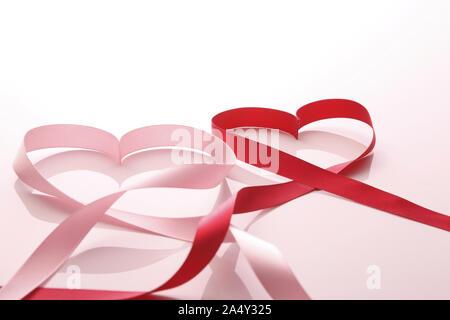 Rouge et gros plan de rubans de satin rose ou bandes en forme de coeur Banque D'Images