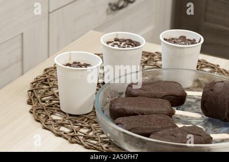 Régime alimentaire végétalien premières glaces. Délicieux dessert maison avec les produits de chocolat. Les sucettes glacées sur un bâton et de portions dans les tasses de papier. La plaque de verre sur l'osier Banque D'Images
