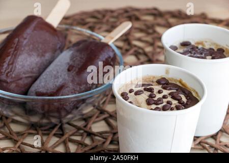 La crème glacée banane crue avec la crème de coco, avec chocolat, dans une tasse de papier blanc, chocolat et les sucettes glacées sur des bâtons dans bol en verre. En bonne santé Banque D'Images