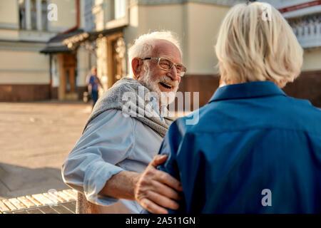 C'est si drôle! Happy senior homme barbu dans les verres en regardant sa femme et souriant, assis sur le banc ensemble
