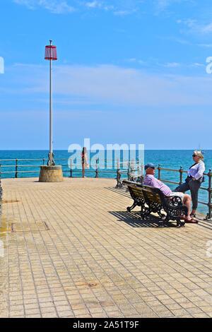 Des gens assis et reposant sur le banjo pier à Swanage dans le soleil d'été. Jeune femme solitaire à la fin de la jetée. Banque D'Images