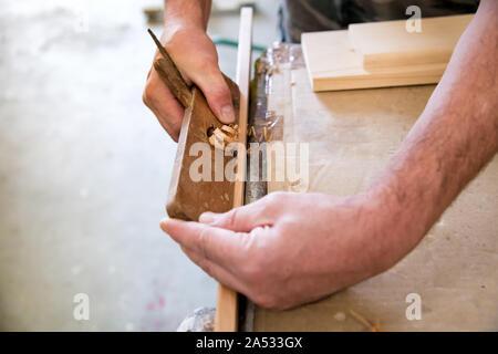 Carpenter à l'aide d'une scie sur une planche de bois dans un atelier de menuiserie dans un gros plan sur ses mains montrant les copeaux de bois sur l'établi