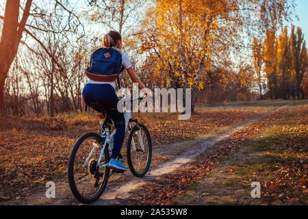 Balade à vélo d'entraînement dans le parc de l'automne. Jeune femme biker sac à dos avec le vélo à l'automne de la forêt. La formation en santé à l'extérieur