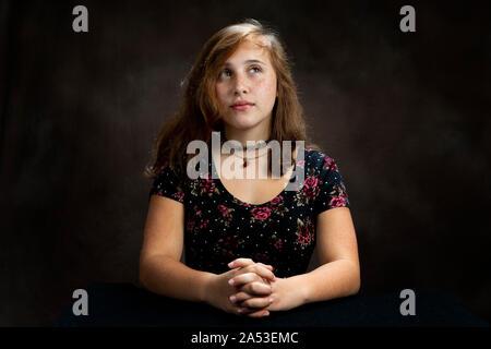 Studio shot of Horizontal un pré-ado jeune fille avec elle les mains jointes, et l'priant. Fond brun avec copie espace.